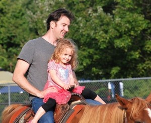 Pat Walsh and his daughter Cecilia, 3, ride a horse.
