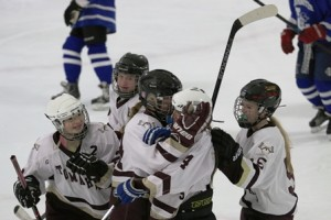 Anna MacDonald (4) celebrates with teammates after scoring a first period goal.