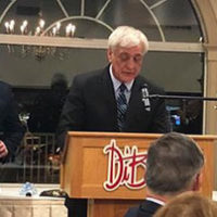 Det Klein speaks at the podium during the Hall of Fame awards banquet. Also on stage are (l to r) Ed Gangi, ICBA vice president; Jonathan Beadreau, who nominated Klein; and Ralph Semb, ICBA Hall of Fame chair and awards banquet master of ceremonies.