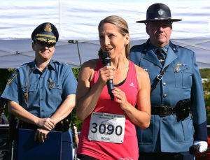 Reisa Clardy speaks during the opening ceremony, flanked by Col. Kerry Gilpin and Sgt. Jamie Conner. Photos/Ed Karvoski Jr.