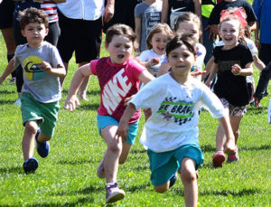Five-year-old children run about 26 yards toward the finish line in the Mighty Mite Marathon. Photos/Ed Karvoski Jr.