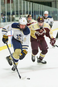 Shrewsbury's Conall Persechino (#9) brings the puck out of the corner while being pursued by Algonquin's Thomas Ackil (#12).