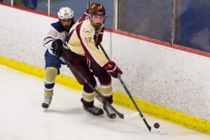 Algonquin's Nate Anderson (#17) keeps the puck away from Shrewsbury's Zack Shelby (#26).