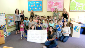 Students from God's Little Children Preschool present the check to Andi Piscopo of Fisher House with (standing, l to r) Alyson Kent, Sue Coggeshall, Kristin Kerins, Donna McArthur, Nikky Olivieri, and (kneeling) Director Beth Hurly. Photo/Melanie Petrucci