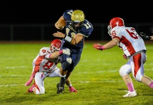 """""""Along for the Ride"""" Shrewsbury High School quarterback Jakob McVane (#11, center) takes St. John's High School's Patrick Ryan (#87, left) for a ride as Sam Norton (#66, right) comes over to assist on the tackle."""