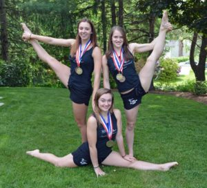 Showing off some of their flexibility and proudly wearing the medals they won in Florida are gymnasts Karina Hopping, Ally McNeil and Maddie Konz. (Photo/submitted)