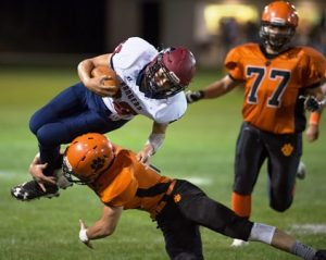 #30 Martin Moran of the Westborough Rangers gets through the front line to punch the football out of quarterback #5 Evan Schmidlein.
