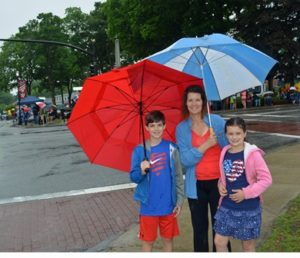 Noah Garvin, a student at Sherwood Middle School, his mom Christine, and sister Grace, who attends Paton School, are all patriotically garbed in red, white and blue as they try to stay dry under their umbrellas at the annual Memorial Day parade and speeches Photo/Joyce DeWallace