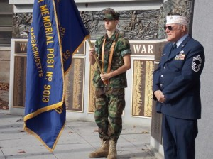 George A. Perry III, the Westborough veterans agent / director veterans services (right), observes the ceremony in front of the war memorials at the Forbes Municipal Building.