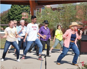 Northborough resident Mary Dragon of the Country Kickers (far right) teaches volunteers the flobie slide.
