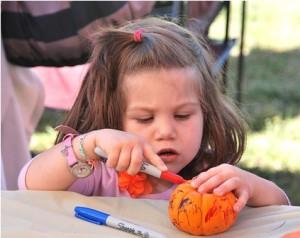 Breenah Venti, 3, paints a pumpkin at the Kids Corner.