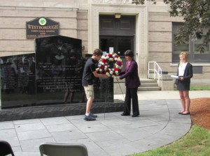 Declan Mazur and State Rep. Carolyn Dykema place a wreath in front of the Desert Storm, Enduring Freedom, and Iraqi Freedom Memorial as Abigail McLucas looks on.