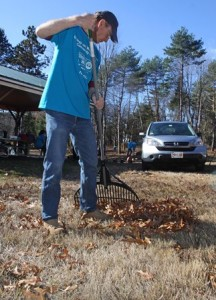 Jim Goddard, employee at Boston Scientific, rakes leaves at the Bowman Conservation Area in Westborough.