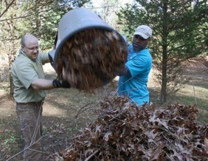 Aaron Campbell, left, and Sean Toomer, employees at Boston Scientific, help clean up the Bowman Conservation Area in Westborough. (Photo/John Swinconeck)