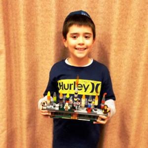 Aaron Schwartz, 8, shows off his homemade Lego menorah at the Beth Tikvah Synagogue Chanukah party.