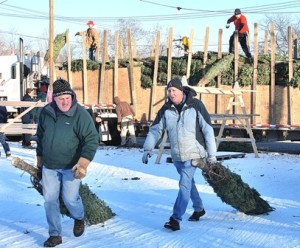 Westborough Civic Club members Rich Connolly and Bill Kohler help unload the first delivery for last year's Christmas tree sale. File photo/Ed Karvoski Jr.