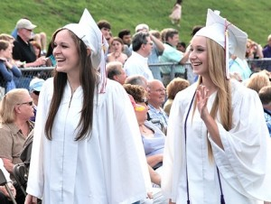 Kendal Simard and Olivia Tortolini spot familiar faces in the crowd as they enter the football field for the graduation ceremony.