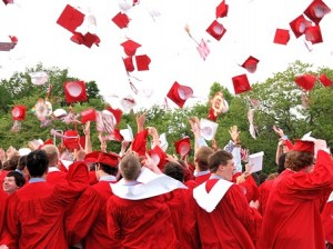 The graduates toss their caps in the air.
