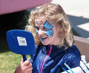 Audrey Sandahl, 7, is pleased with the reflection of the design painted on her face.