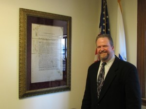 Ed Turner stands next to a restored frame with one of the town's historical documents.