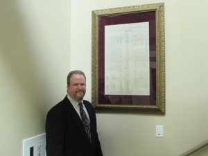 Ed Turner stands next to a restored frame with one of the historical documents.