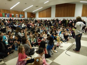 Kids and their families listen to Principal Leigh Ann Becker as she gives some opening remarks.