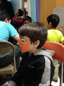 Andrew gets his face painted like a tiger.