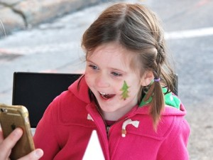 Mary Yenalevitch, 4, sees the reflection of her painted face at the Little V Designs booth.