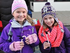 Emily Gray and Ana LeLacheur, both 8, display reindeer candy canes they created at the New Hope Chapel booth.