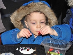 Owen Murphy, 2, decorates an ornament at the Westboro Tennis & Swim Club booth.