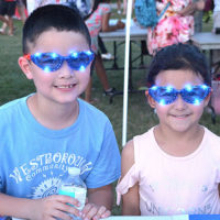 The Hyatt siblings – Ethan, 7, and Julia, 5 – get souvenir sunglasses at the Westborough July 4th Planning Committee booth. Photos/Ed Karvoski Jr.