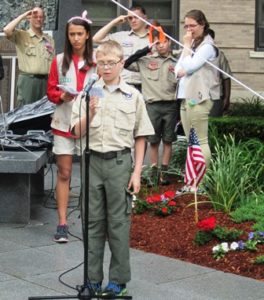 A Boy Scout reads names of veterans who passed away in 2015.