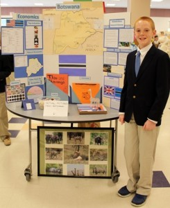 Miles Henderson, 12, stands by his project on Botswana.