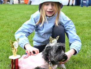 Gwen Raczkowski, 7, poses her dog Sadie with trophies won for Most Fashionable and Best Wiggly Butt. Photos/Ed Karvoski Jr.