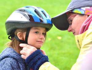 Allison Purcell, 6, gets fitted for a bicycle helmet by Nancy Siegal of the Westborough Pedestrian Advisory Committee. Photos/Ed Karvoski Jr.