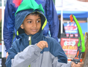 Dhyan Shenoy, 9, views the arrow he shot as it hits a target at Westborough Lions Club's booth with a Robin Hood theme. Photos/Ed Karvoski Jr.