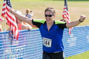 Daniel Milton of Hudson celebrates as he approaches the finish line.