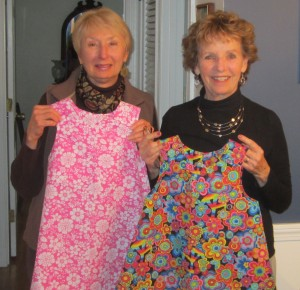 Barbara Stone (l) and Judy Hall (r ) hold two of the dresses made last year for the project