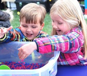 The Bresnahan siblings – Cade, 3, and Sloane, 5 – play with water beads in a sensory bin at the F3 Friends–Fitness–Fun booth.