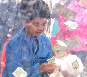"""Kavin Siva Subramanian, 9, catches windblown cash inside """"The Vault"""" at the Central One Federal Credit Union booth."""