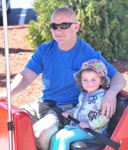 Steve Fortier and his daughter Riley, 2, ride the roaming railroad.
