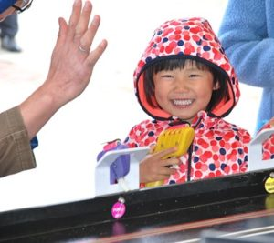 Annie Tan, 3, gets a high-five from her dad when she wins a slot car race.