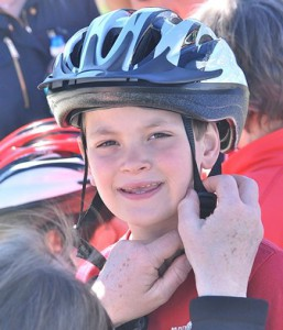 John Strong IV, 7, gets fitted for a free helmet at the first Youth Bike Rodeo.