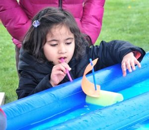 """Myra Saxena, 3, propels a toy sailboat in the """"Raingutter Regatta"""" at the Cub Scout Pack 33 booth."""