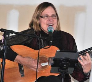 Local singer and songwriter Luanne Crosby performs at the Music Fest, moved indoors because of inclement weather.
