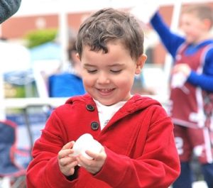 Logan Esquilin, 3, examines a toy tooth that he got at the Westborough Dental Associates booth.