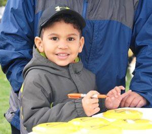 Alejandro Arias-Benitez, 4, prints his name on a Frisbee at the Westboro Tennis & Swim Club booth.