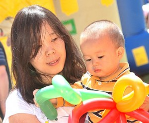 Ellie Liu and her son Brady, 17 months, receive a balloon sculpture created by a Westborough High School Student Council member.