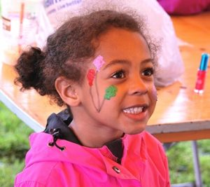 Lauren Dennis, 4, is pleased with the flower design painted on her face at the Kids Carnival.