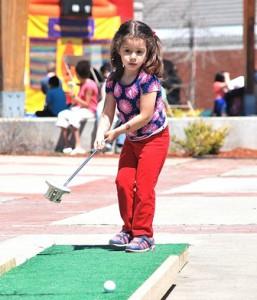 Juliette Bazterra, 4, tries her hand at playing miniature golf.